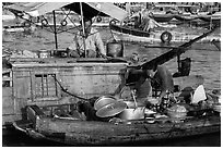 Woman serving food across boats, Cai Rang floating market. Can Tho, Vietnam ( black and white)