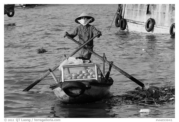 Woman paddling boat with breads, Cai Rang floating market. Can Tho, Vietnam (black and white)