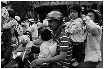 Family on motorbike watching musical performance. Ho Chi Minh City, Vietnam (black and white)