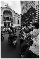 Family on motorbike watching performance at opera house. Ho Chi Minh City, Vietnam (black and white)