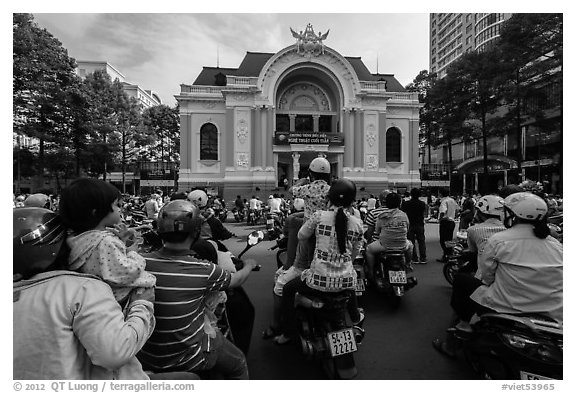 Families gather on motorbikes to watch performance in front of opera house. Ho Chi Minh City, Vietnam (black and white)