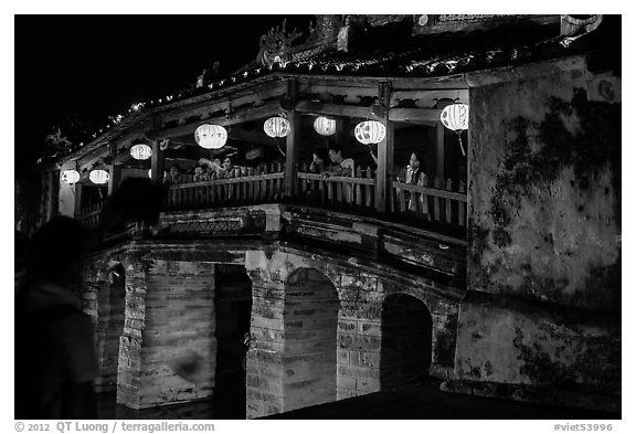 People enjoy Japanese Bridge lit solely by lanterns. Hoi An, Vietnam (black and white)