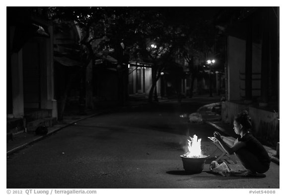Woman burning paper on street at night. Hoi An, Vietnam (black and white)
