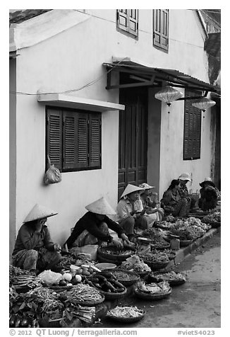 Vegetable vendors sitting in front of old house. Hoi An, Vietnam (black and white)