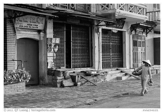 Woman carrying fruit in front of old storefronts. Hoi An, Vietnam (black and white)