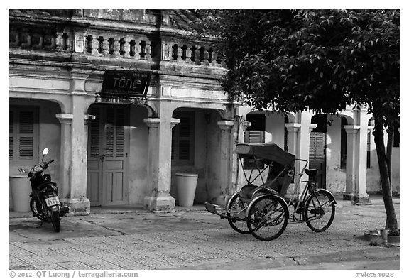 Motorcyle and cyclo in front of old townhouses. Hoi An, Vietnam (black and white)