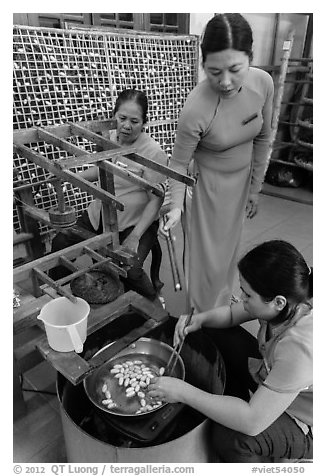 Workers demonstrate silkworm processing. Hoi An, Vietnam (black and white)