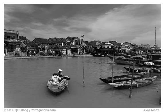 Women crossing the Thu Bon River in a rowboat. Hoi An, Vietnam (black and white)