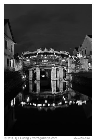 Illuminated Japanese covered bridge reflected in canal. Hoi An, Vietnam (black and white)