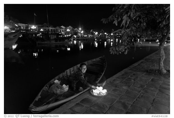 Woman sitting in rowboat selling candles on quay. Hoi An, Vietnam (black and white)