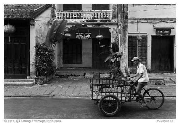 Man riding tricycle cart in front of old townhouses. Hoi An, Vietnam (black and white)