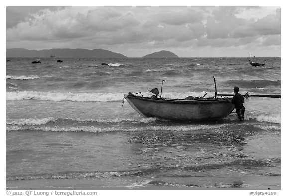 Man entering ocean with boat in stormy weather. Da Nang, Vietnam (black and white)