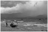 Men pushing coracle boat into stormy ocean. Da Nang, Vietnam (black and white)