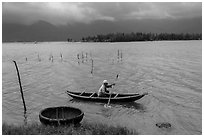 Fisherman rowing canoe in lagoon. Vietnam (black and white)