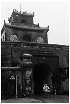 Biking through citadel gated entrance in the rain. Hue, Vietnam (black and white)