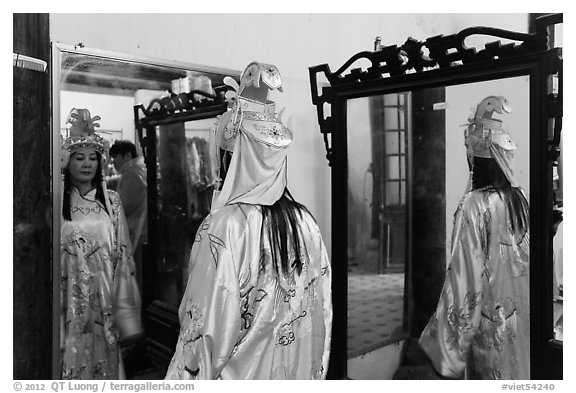 Woman in imperial dress checking herself in mirror, citadel. Hue, Vietnam (black and white)