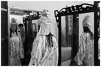 Woman in imperial dress checking herself in mirror, citadel. Hue, Vietnam ( black and white)