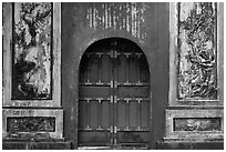 Red door and ceramic decorations, imperial citadel. Hue, Vietnam (black and white)