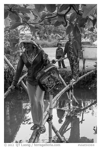 Women crossing monkey bridge, Thanh Toan. Hue, Vietnam (black and white)