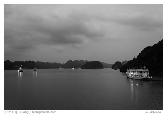 View of bay with lights of anchored tour boats at dawn. Halong Bay, Vietnam (black and white)