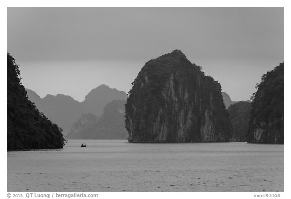 Fishing boat dwarfed by limestone islands. Halong Bay, Vietnam (black and white)