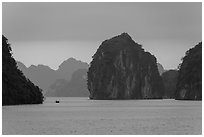Fishing boat dwarfed by limestone islands. Halong Bay, Vietnam ( black and white)