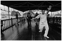 Morning Tai Chi session on tour boat deck. Halong Bay, Vietnam (black and white)
