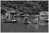Villagers move between floating houses by rowboat. Halong Bay, Vietnam ( black and white)