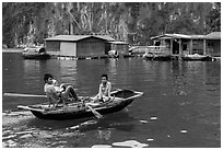 Man holding infant while rowing with feet, Vung Vieng village. Halong Bay, Vietnam (black and white)