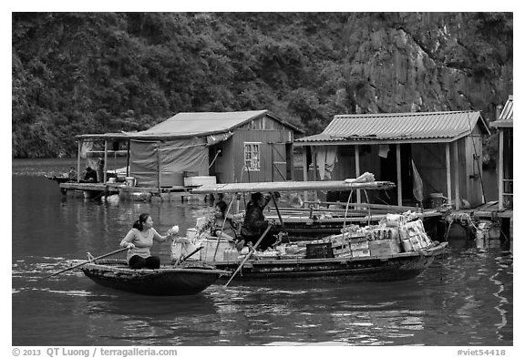 Woman buying produce from grocery boat, Vung Vieng village. Halong Bay, Vietnam (black and white)
