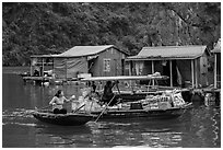 Woman buying produce from grocery boat, Vung Vieng village. Halong Bay, Vietnam ( black and white)