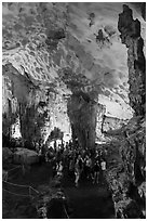 Tourists in first grotto, Surprise Cave. Halong Bay, Vietnam (black and white)