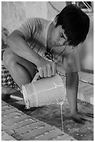 Man pouring clay into molds in ceramic workshop. Bat Trang, Vietnam (black and white)