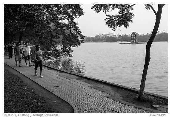 Walking for exercise around Hoang Kiem Lake at dawn. Hanoi, Vietnam (black and white)