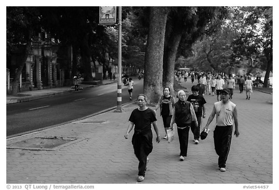 Numerous people walk counter-clockwise around Hoang Kiem Lake. Hanoi, Vietnam (black and white)