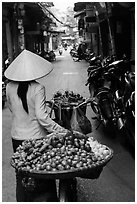 Woman pushing bicycle loaded with vegetable for sale in narrow street, old quarter. Hanoi, Vietnam ( black and white)