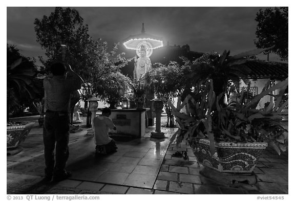 Men pray at outside Phung Son Pagoda at night, district 11. Ho Chi Minh City, Vietnam (black and white)
