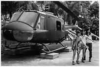 Young women posing with helicopter, War Remnants Museum, district 3. Ho Chi Minh City, Vietnam ( black and white)