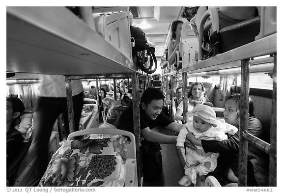 Couple passing baby on sleeper bus. Vietnam (black and white)
