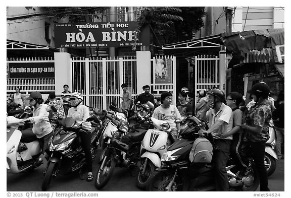 School entrance with parents waiting on motorbikes. Ho Chi Minh City, Vietnam (black and white)