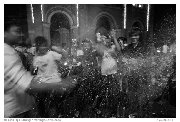 Revellers celebrating with spray in front of Notre Dame Cathedral on Christmas Eve. Ho Chi Minh City, Vietnam (black and white)