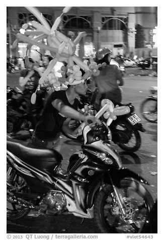 Man with coiffe of balloons, Christmas Eve. Ho Chi Minh City, Vietnam (black and white)