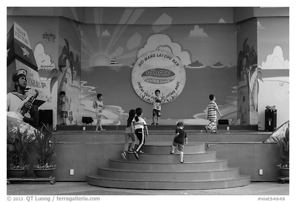 Children on stage next to militaristic mural, Dam Sen Water Park, district 11. Ho Chi Minh City, Vietnam (black and white)