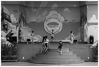 Children on stage next to militaristic mural, Dam Sen Water Park, district 11. Ho Chi Minh City, Vietnam ( black and white)