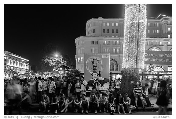 Revellers sitting on street, New Year eve. Ho Chi Minh City, Vietnam (black and white)