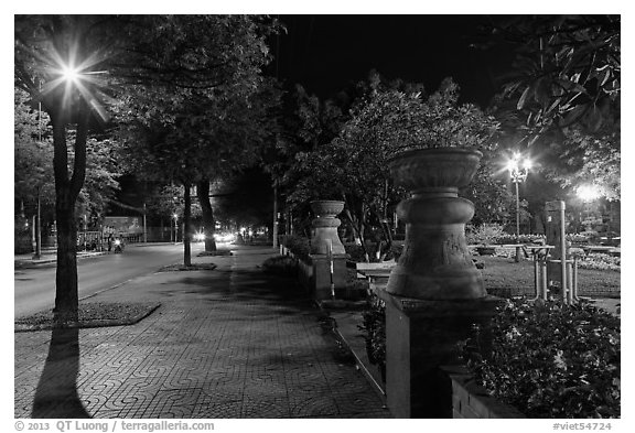 Sidewalk and park at night. Ho Chi Minh City, Vietnam (black and white)