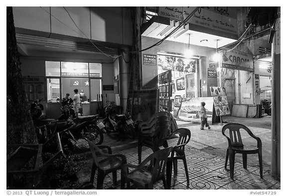 Communist party office and store selling images at night. Ho Chi Minh City, Vietnam (black and white)