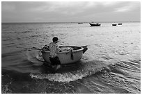 Man holding coracle boat. Mui Ne, Vietnam (black and white)
