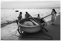 Family around their coracle boat. Mui Ne, Vietnam (black and white)