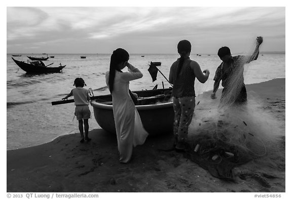 Fishermen folding net out of coracle boat as children watch. Mui Ne, Vietnam (black and white)